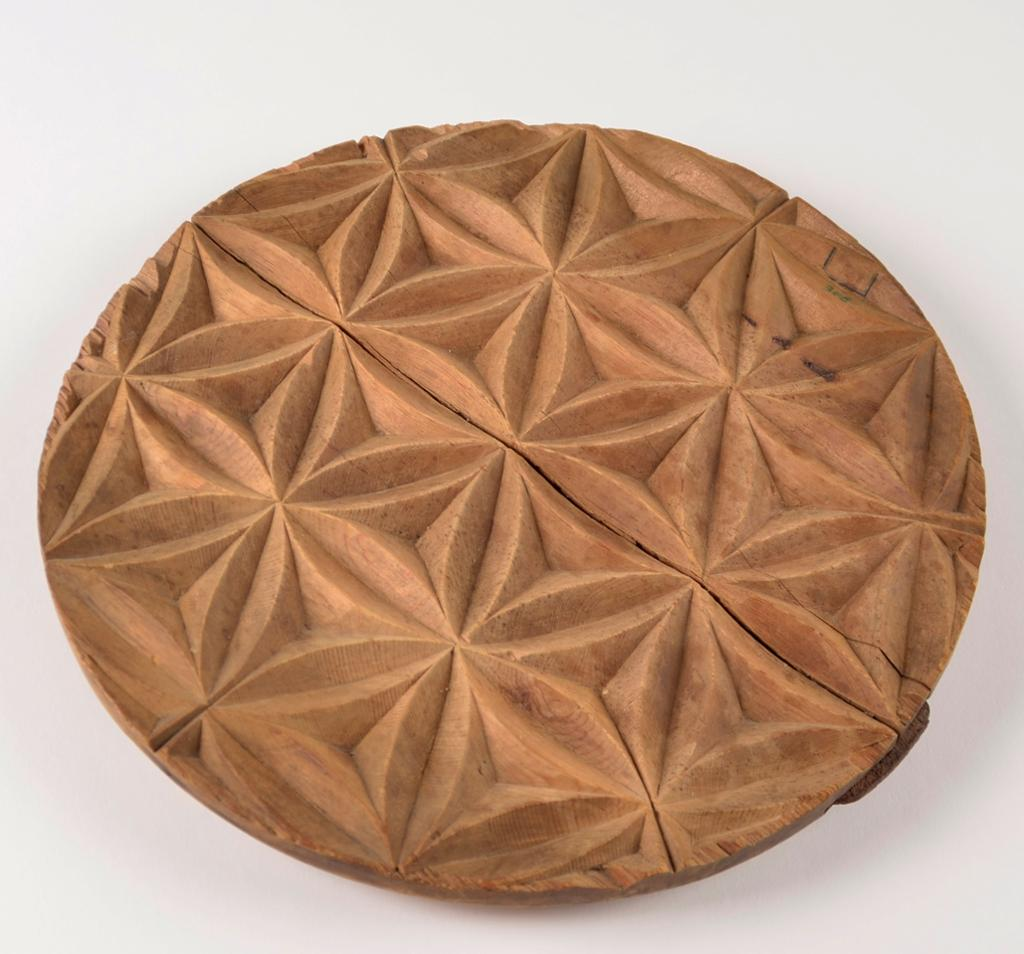 Sirkelformet treplate med geometrisk mønster utskåret. Foto.