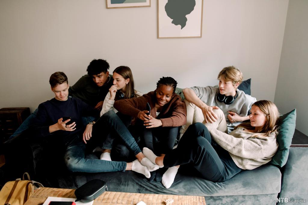 En gjeng ungdommer slapper av i en sofa. Foto.
