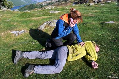 En mann er lagt i sideleie, og en dame snakker i mobiltelefonen mens hun følger med på mannen. Foto.