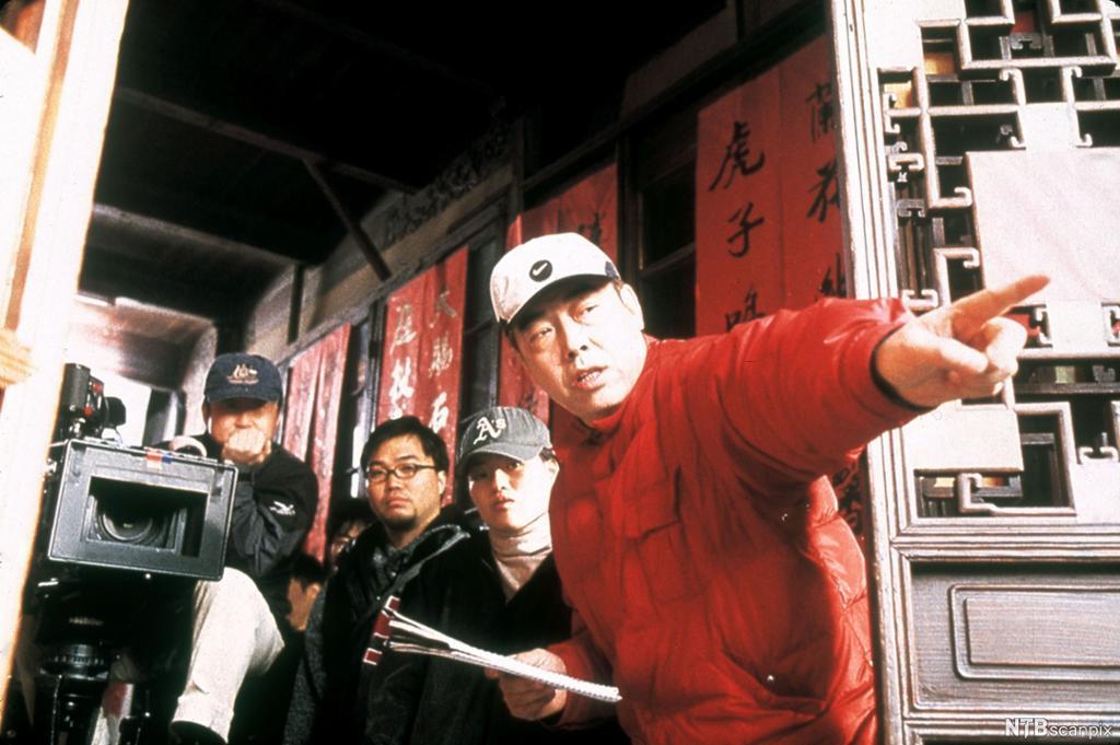 En kinesisk regissør instruerer foran et kamera. Foto.