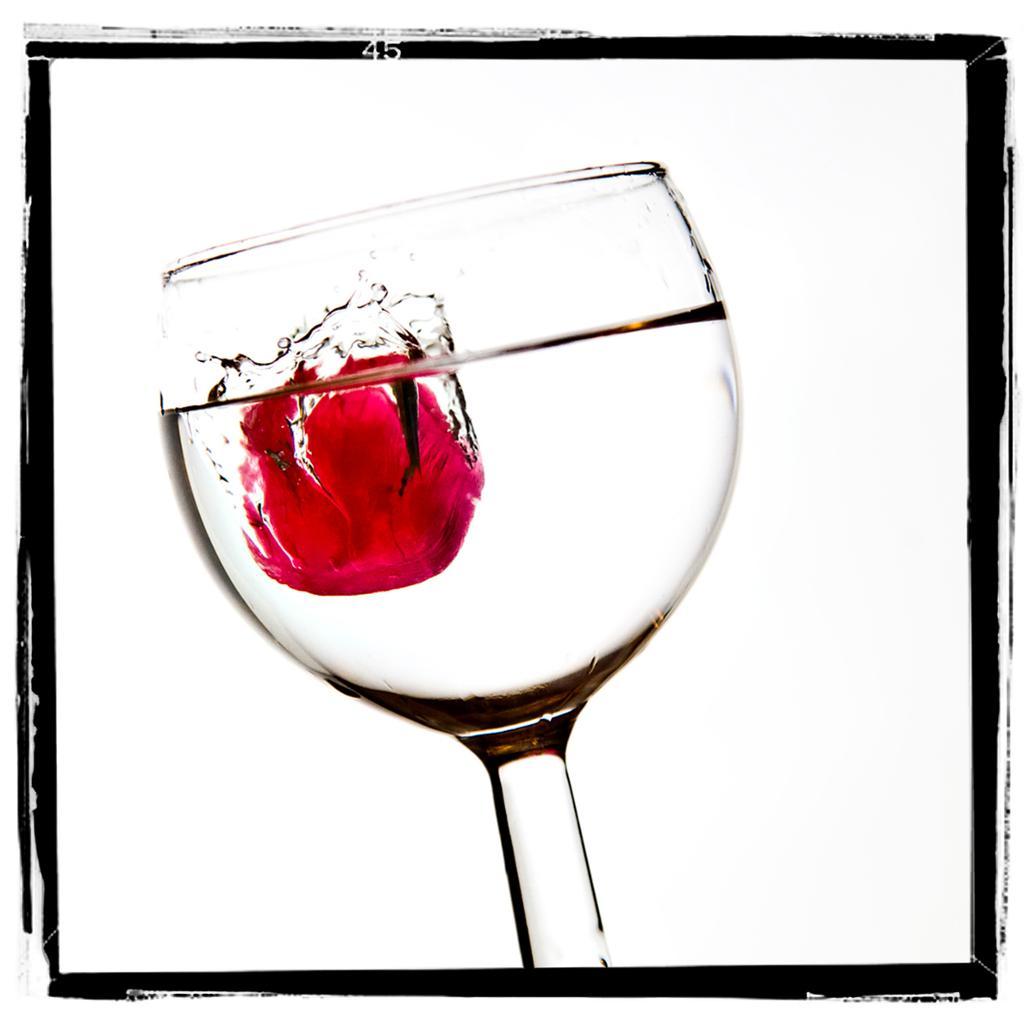 Rødt drops kastes oppi et vinglass med klar væske. Foto.