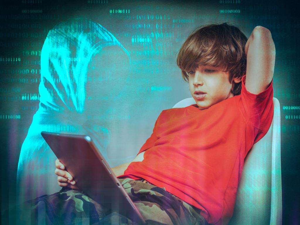 En gutt sitter tilbakelent i en stol og ser på et stort nettbrett han har i fanget. Bakgrunnen er mørk med mange lysegrønne tallrekker med ettall og nuller og en person med mørk hettegenser som har hetta slik at hele ansiktet er skygget for. Foto med effekter.