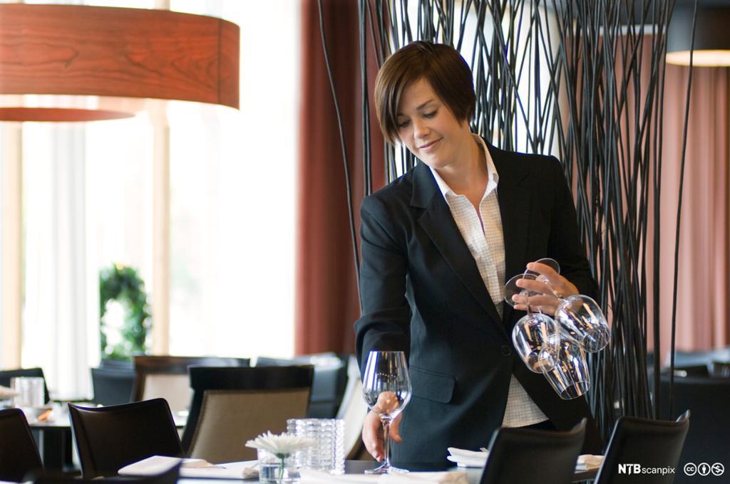 Servitør setter vinglass på et restaurantbord. foto.