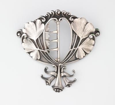 Beltespenne i sølv, dekorert med blomsterornament. Foto.