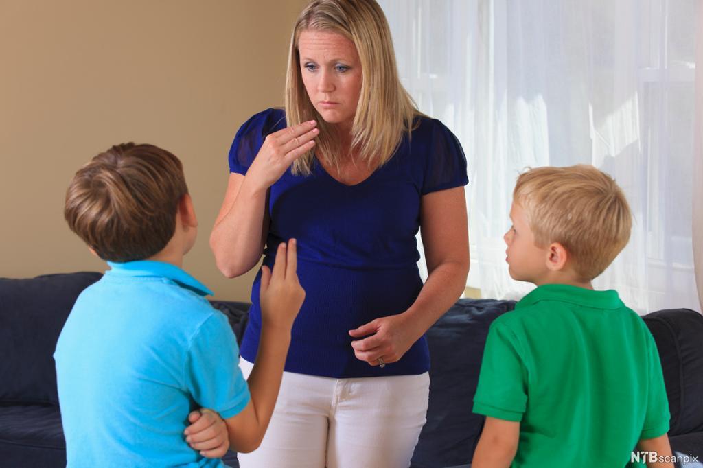 Vaksen og to barn kommuniserer med teiknspråk. Foto.