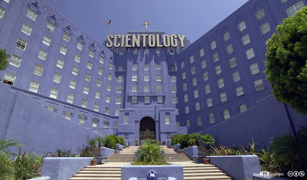 """Stor, blå bygning. Øverst på bygningen står et kors og ordet """"Scientology"""" med store bokstaver. Foto."""