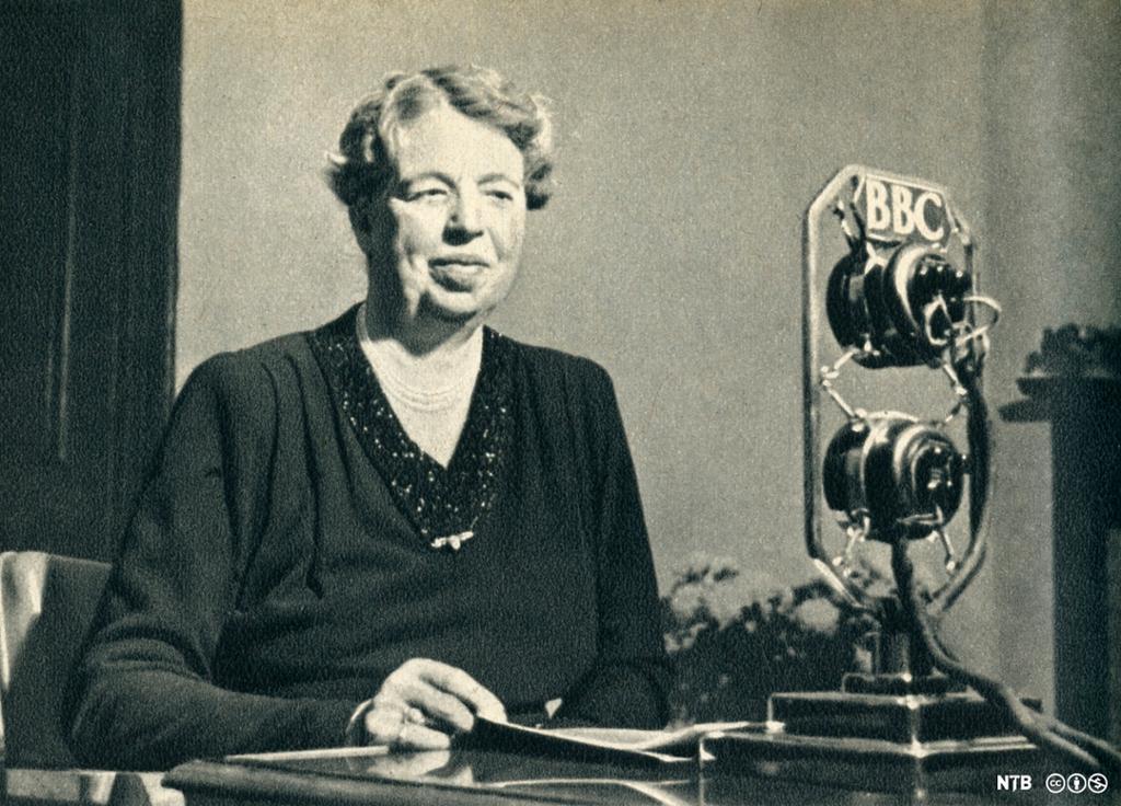 En kvinne i studie foran en gammeldags mikrofon. Foto.