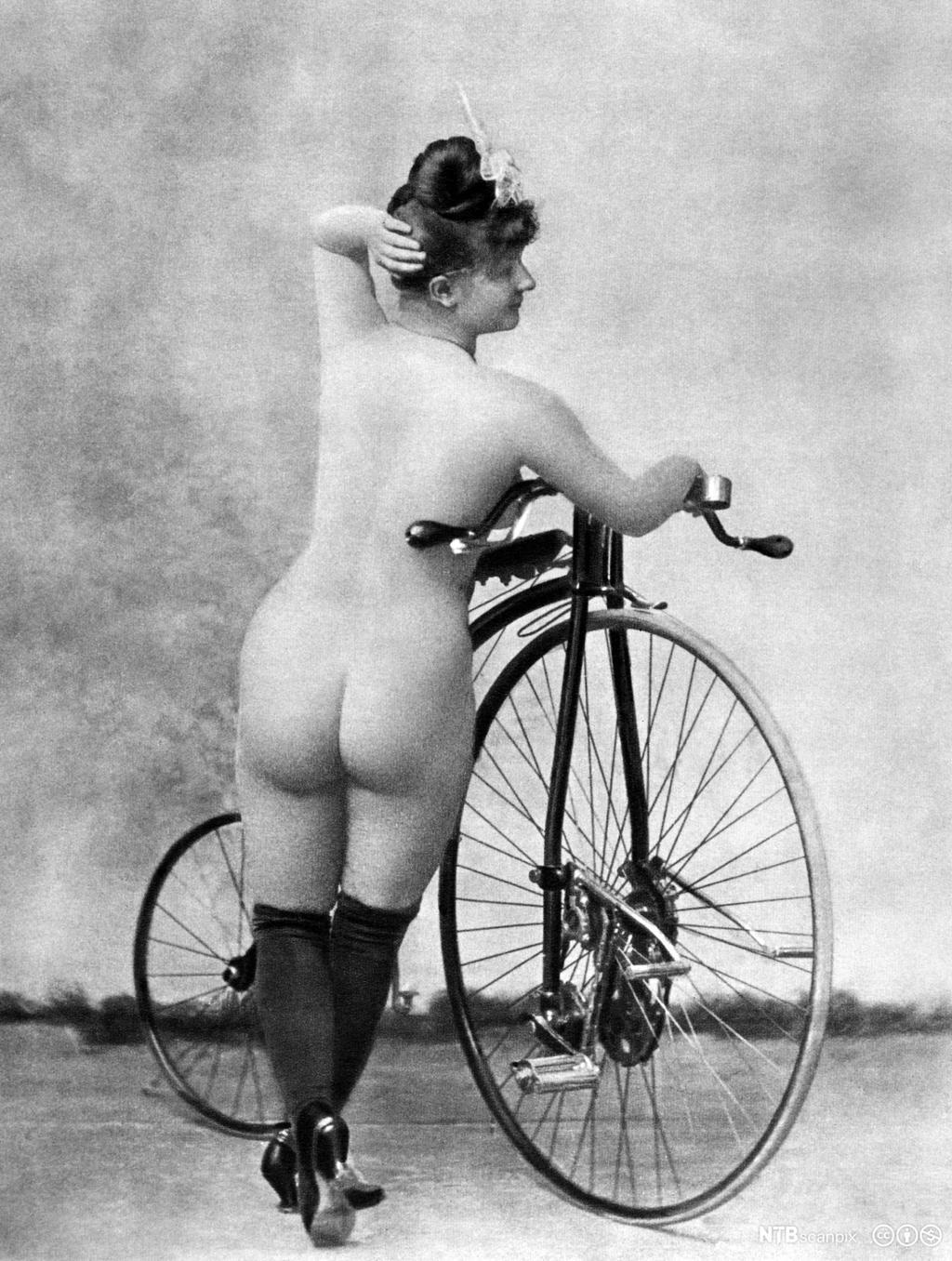 Naken kvinne med gammeldags sykkel. Bilde.
