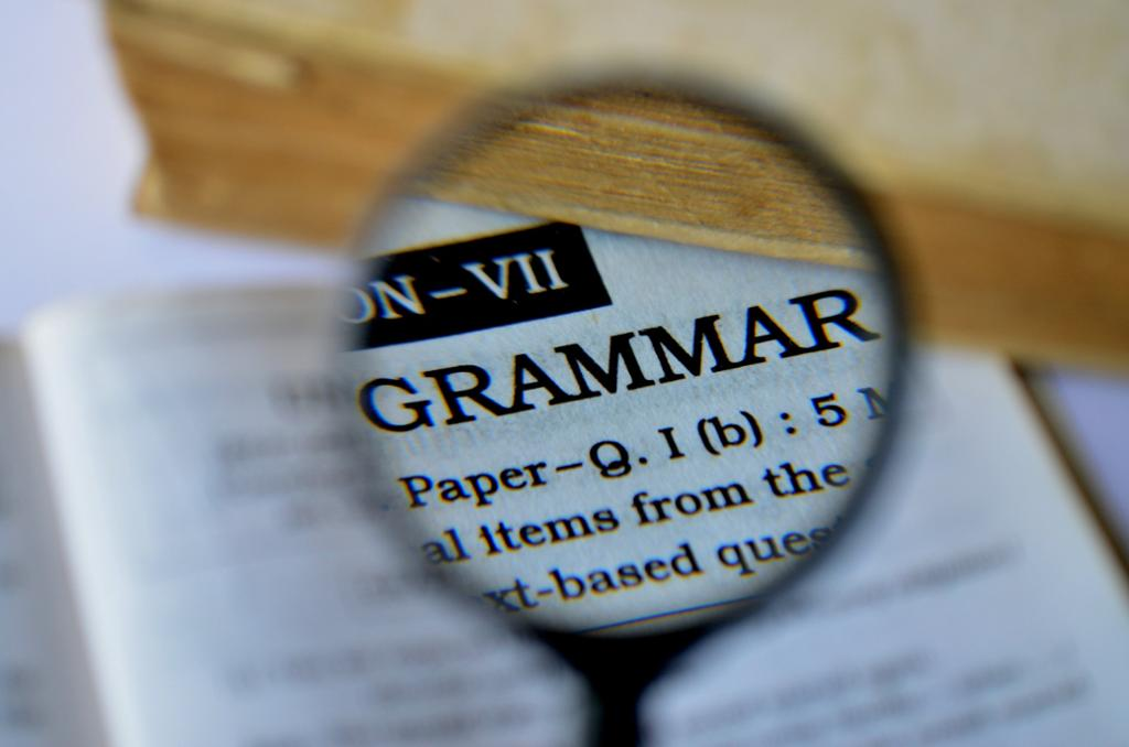 "A magnifying glass highlighting the word ""grammar"". Photo."