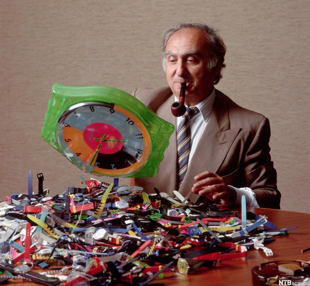 Nicolas Hayek, president i Swatch, sitter ved et bord med mange klokker i en haug foran seg. Foto.