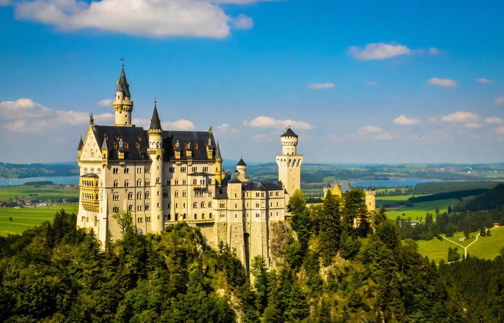 Slott Neuschwanstein i Bayern. Lys steinbygning med slanke tårn. Foto.