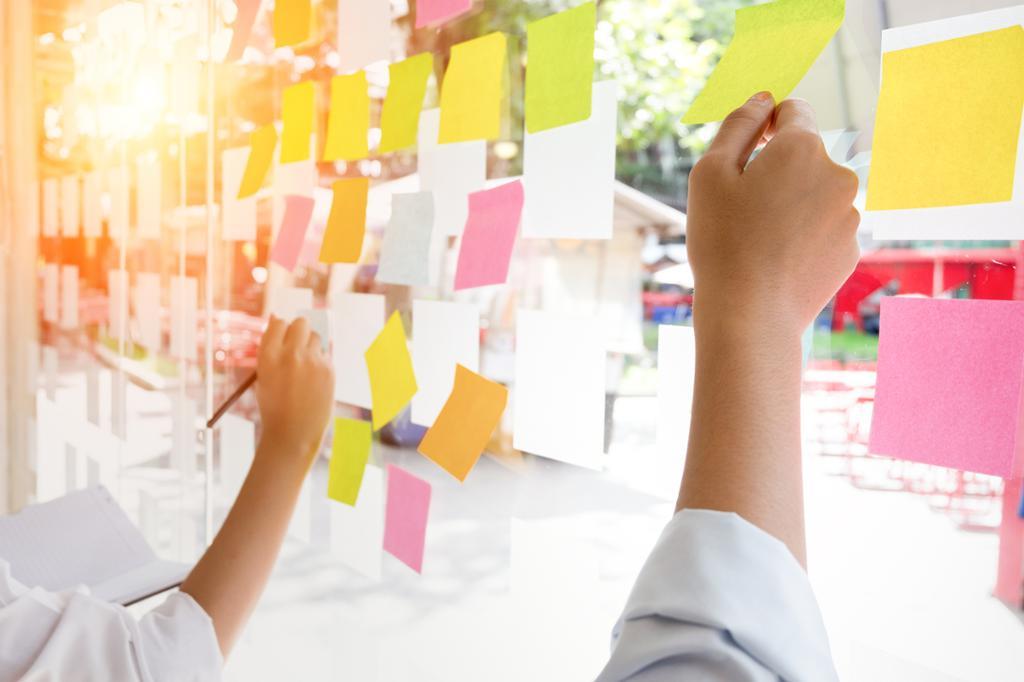 Fotografi av hender som skriver på post-it-lapper i ulike farger på en glassvegg.