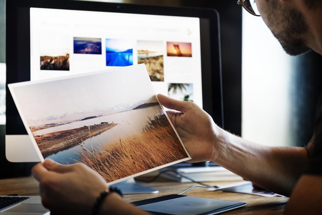 Person ser på bilder foran en skjerm. Foto.