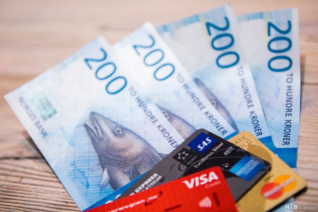 Fire tohundrelapper og en rekke kredittkort. Foto.