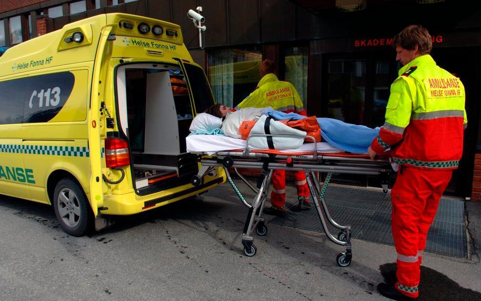Pasient på båre som trilles inn i en ambulanse. Foto.