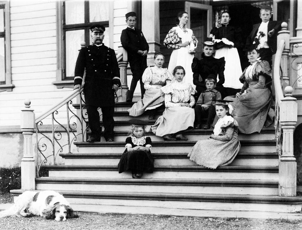 Amtmann Graff med familie, hushjelper og hund på trappa til Amtmannsgården i Vadsø, 1898. Foto.