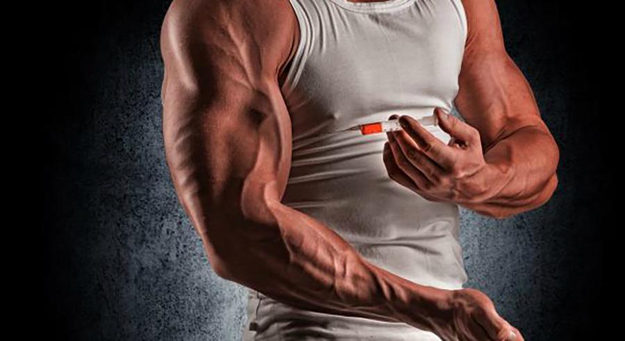 Muskelmann som setter en sprøyte i armen. Foto.