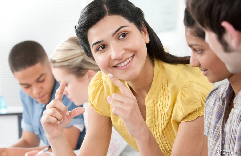 Dame forklarer til andre ved hjelp av kroppsspråk. Foto.