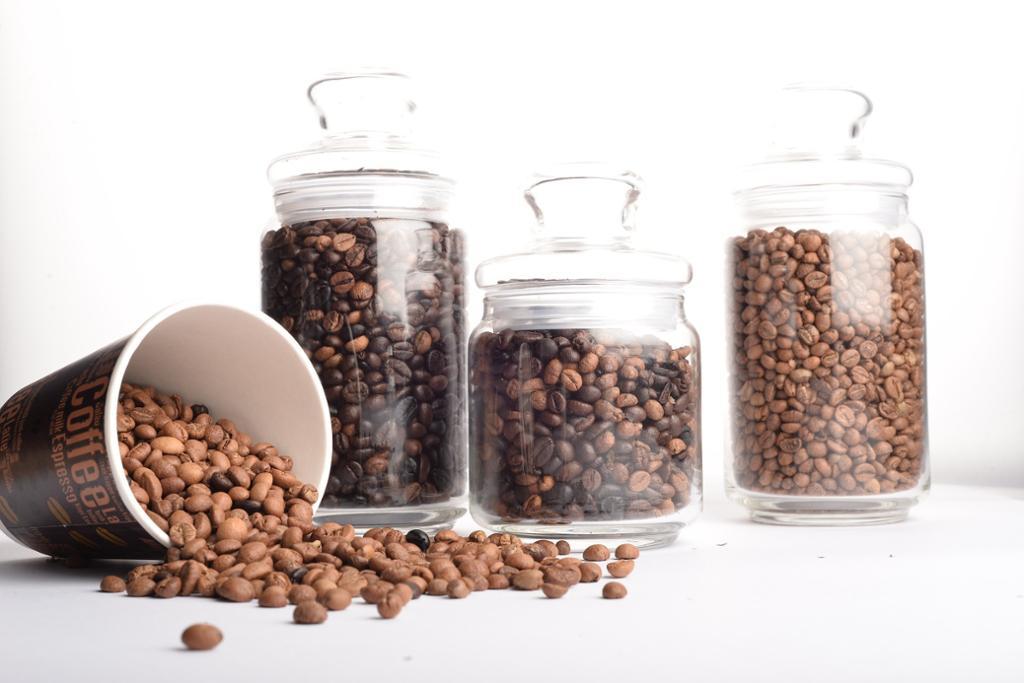 Kaffibønner i krukker av glas og i eit pappkrus som har velta. Foto.