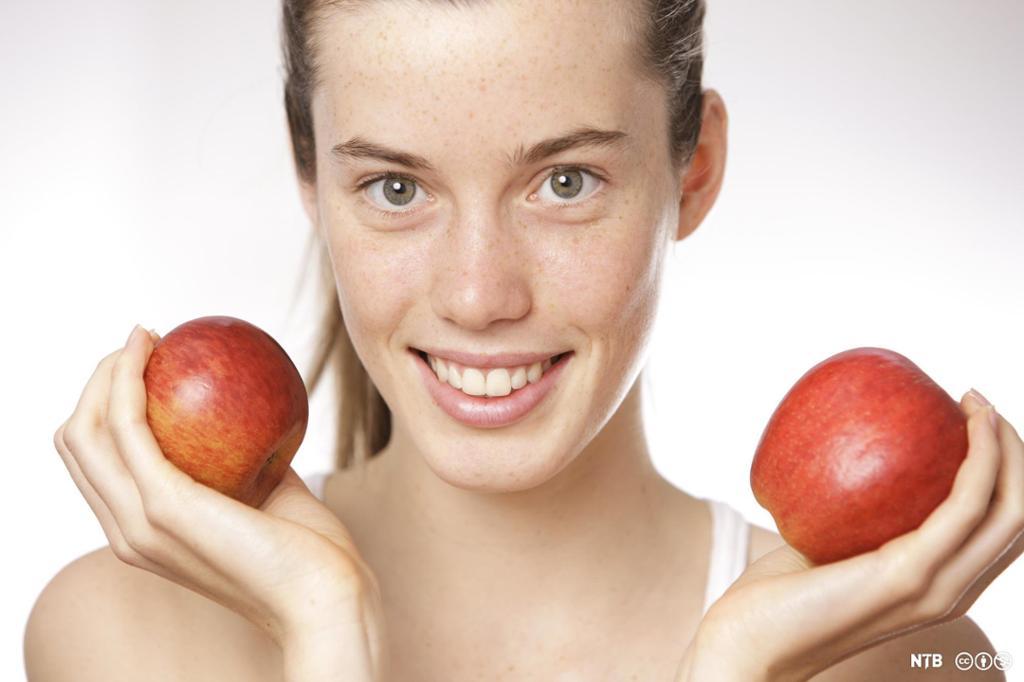 Ung kvinne som holder et rødt eple i hver hånd og smiler. Foto.