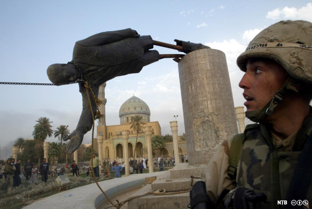 En liten folkemengde er på at en statue blir revet ned fra sokkelen. En soldat står i forgrunnen. Foto.