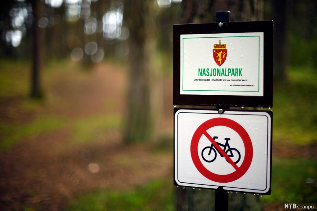 Skilt som viser at det er forbudt å sykle i en nasjonalpark. Foto.
