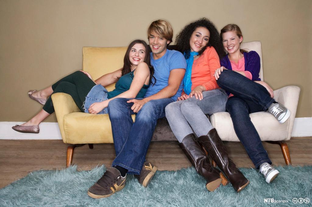 Tenåringer som sitter i en sofa. Bilde.