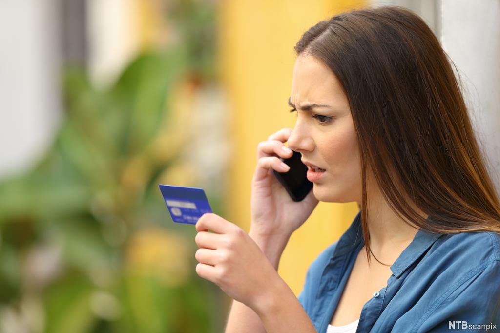 En sint dame holder et kredittkort i den ene hånden og en telefon i den andre. Foto.