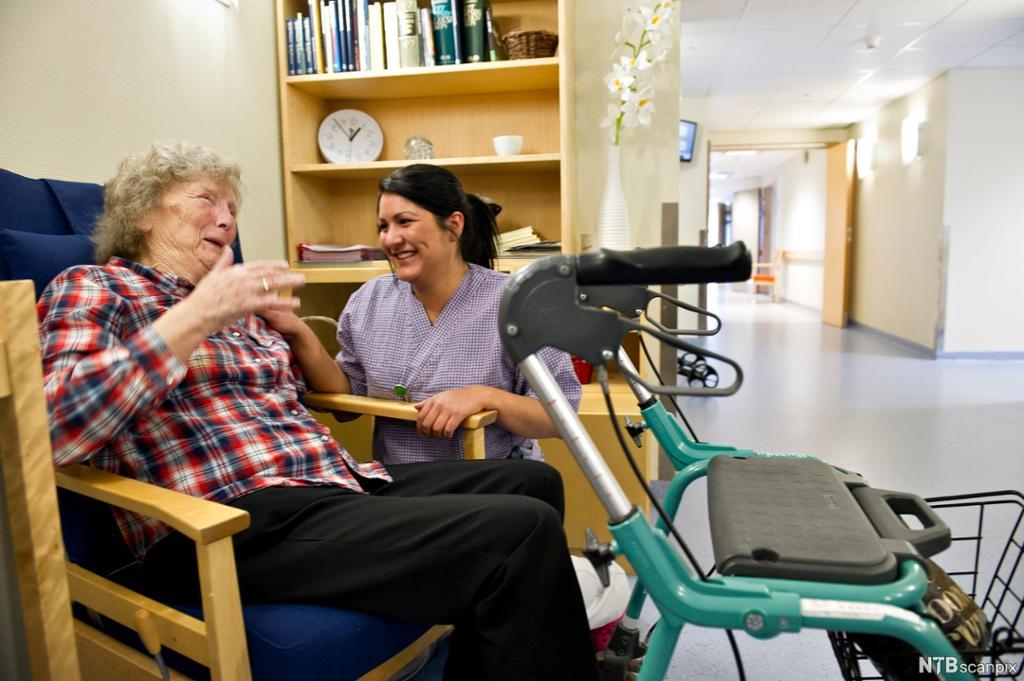 Helsefagarbeider og eldre pasient i hyggelig samvær. Foto.