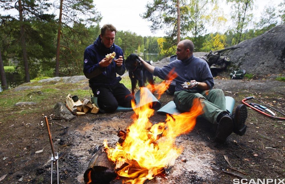To personer spiser mat ved bål. Foto.