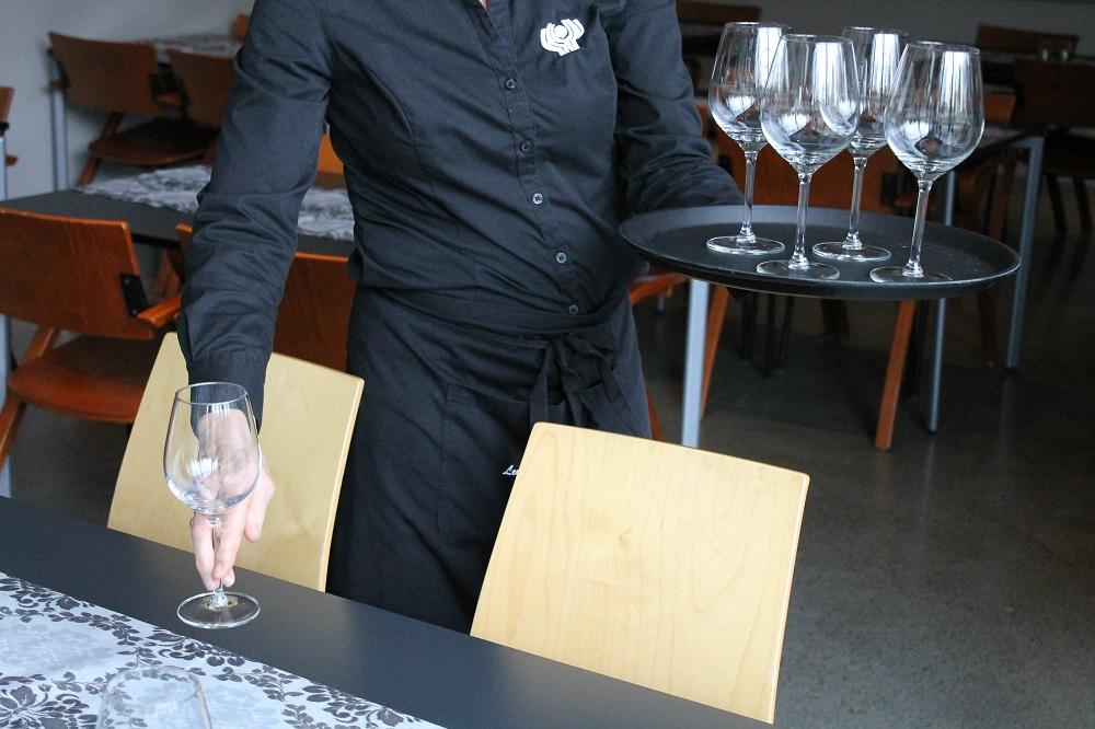 Servitør viser teknikk med å setje på plass stettglas. Foto.