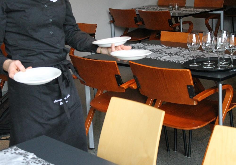En servitør som bærer tre suppetallerkener. Foto.