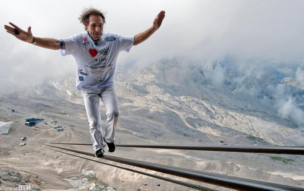 En mann balanserer på kabelbane i fjellet.