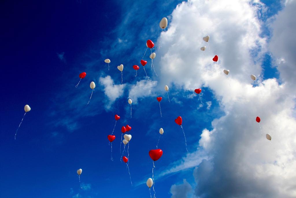 Røde og hvite hjerteballonger svever mot knallblå himmel og hvite skyer.foto.