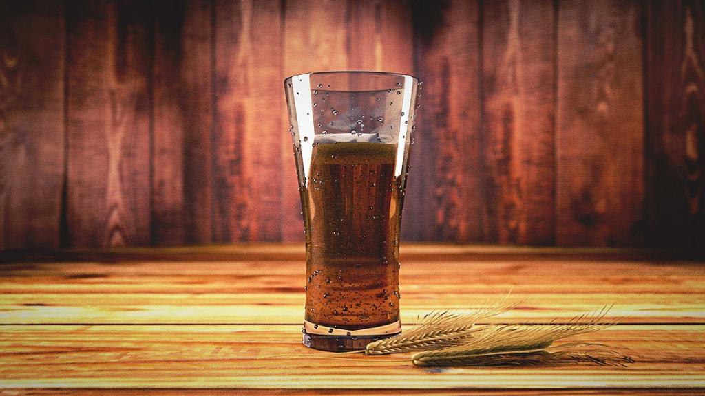 Ølglass og kornaks på et bord. foto.
