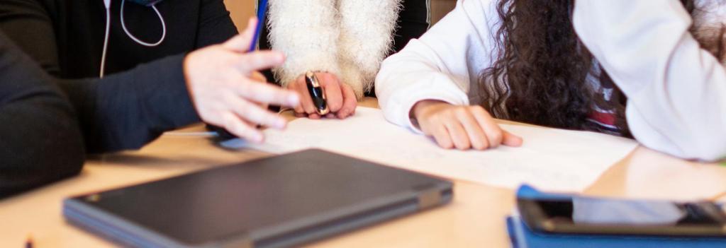 Tre personer samarbeider. Bildet viser hender, papir og en PC på et bord. Foto.