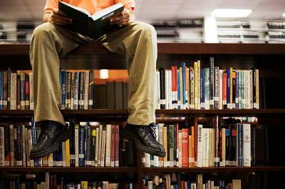Mann som sitter på toppen av ei bokhylle og leser i ei bok. Foto.