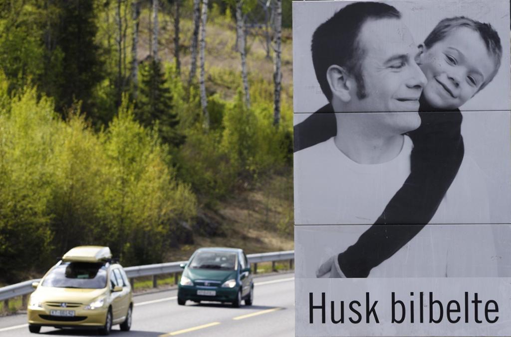 Traffikert vei med skilt som oppfordrer billister til å huske bilbelte. Foto.