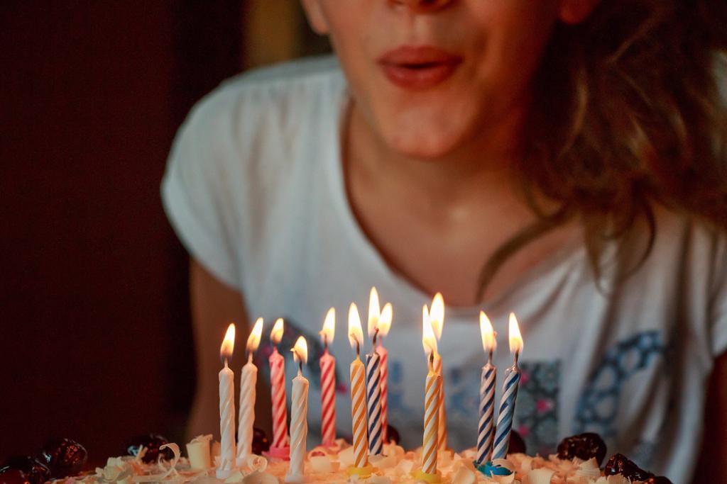 Jente blåser ut lys på bursdagskake. Foto.