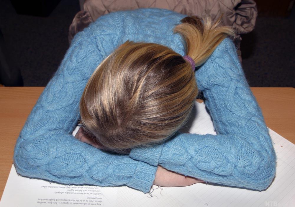 Elev som har sovnet ved pulten. Foto.