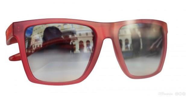 Ett par røde briller med gate reflektert i glassene. Foto