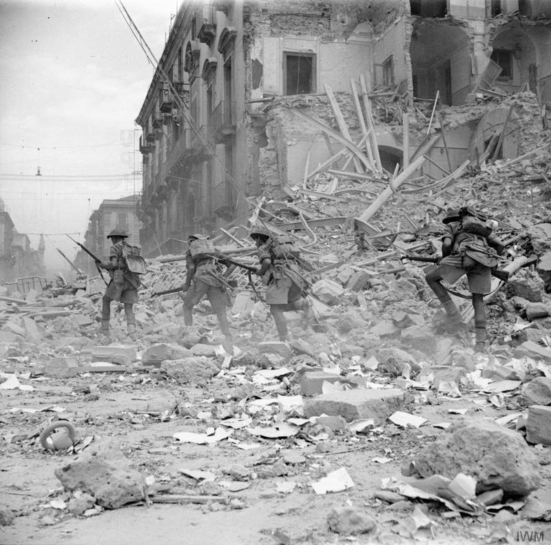 Britisk infanterisoldater går gjennom ruiner i Catania, Sicilia, 1943. Foto.