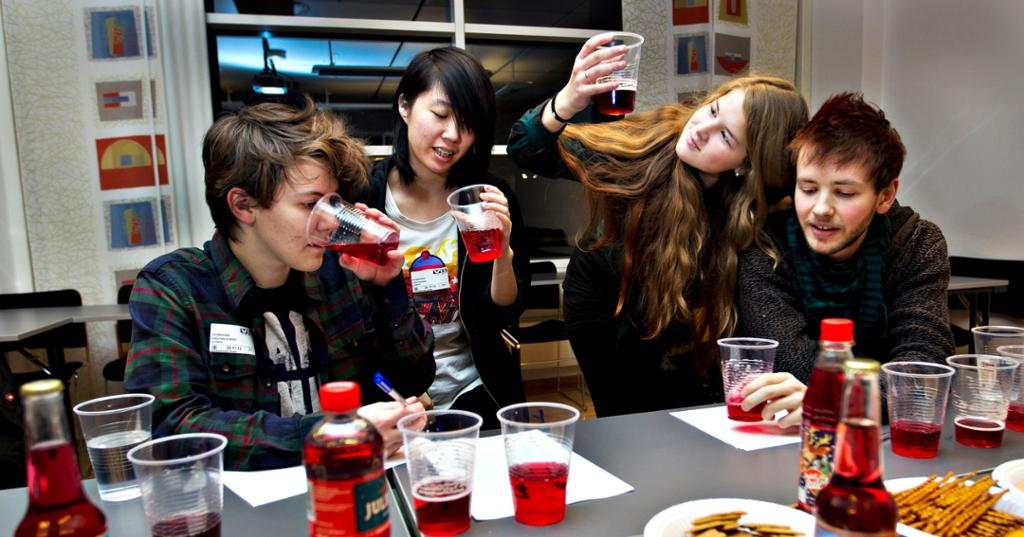 Fire ungdommer smaker på flere typer rødbrus. Foto.