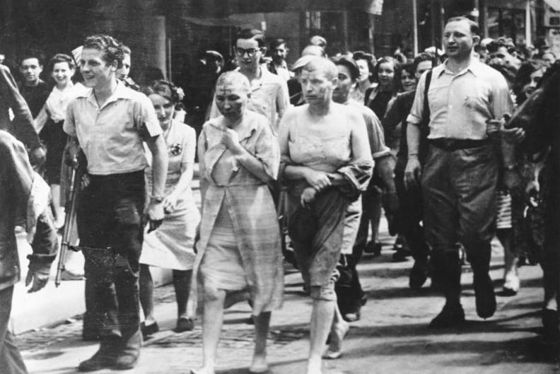 Franske kvinner anklaget for å være kollaboratører under krigen blir ført gjennom Paris med barberte hoder og med svimerker på kroppen. Foto.