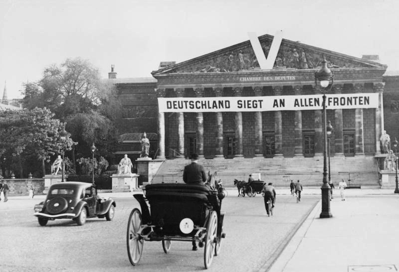 """Tysk banner på Bourbon-palassest i Paris i 1941. På banneret står """"Tyskland vinner på alle fronter"""". Foto."""