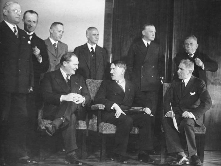 Pressemøte etter det første møte i Hitlers nye regjering, 30. januar 1933. Hitler sittende i stol med kabinettmedlemmer rundt seg. Foto.