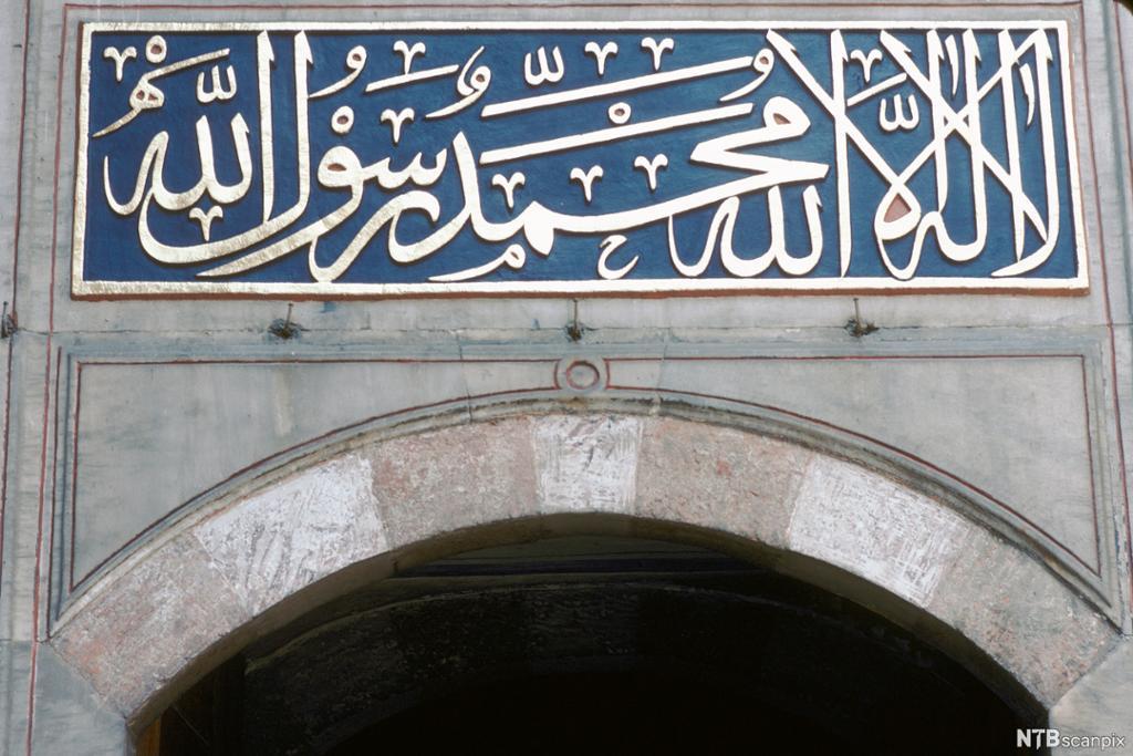 Arabisk skrift i gull på blå bunn. Utsmykning over port. Foto.