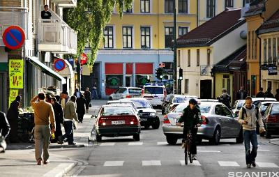 En gate med butikker, biler og gående og syklende personer. Foto.