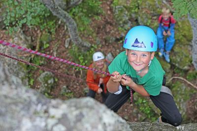 Blid gutt som klatrer i fjellvegg. Foto.