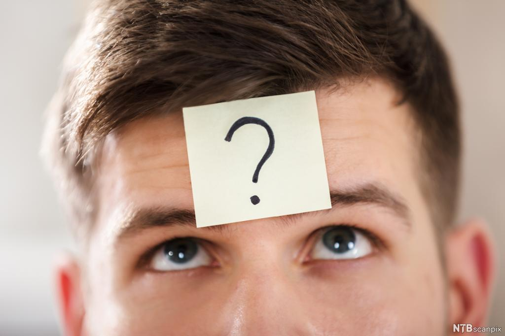 Mann med klistrelapp med spørsmålstegn i panna. Foto.